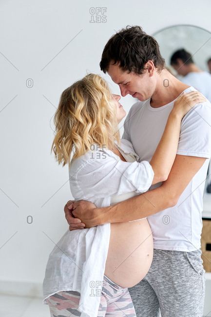 Happy pregnant couple embraced and preparing to kiss