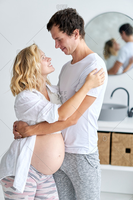 Pregnant couple embraced and looking into each other's eyes