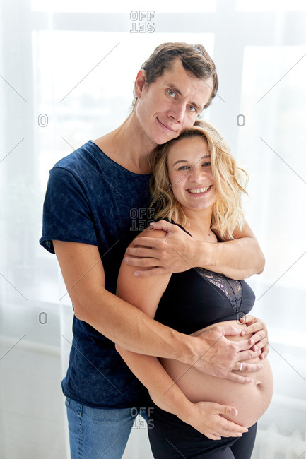 Happy couple lovingly embracing wife's pregnant belly