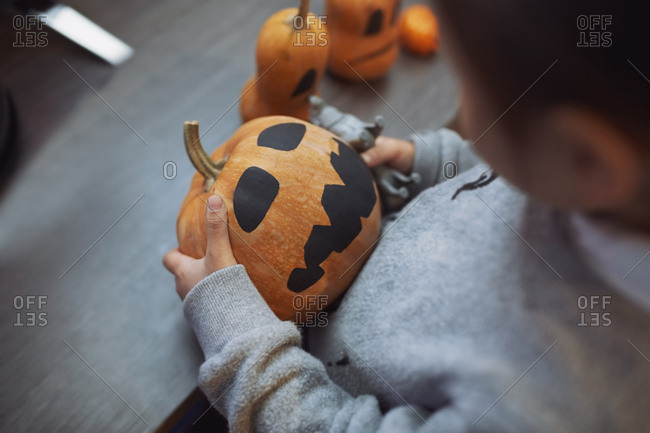 Girl playing with Halloween pumpkins