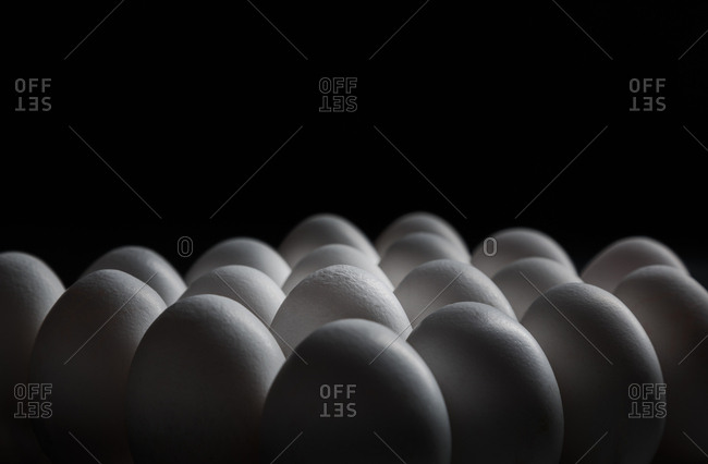 group of eggs between shadows with black background and side light