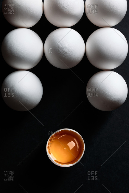 Group of eggs on black background. One of them broken and isolated.