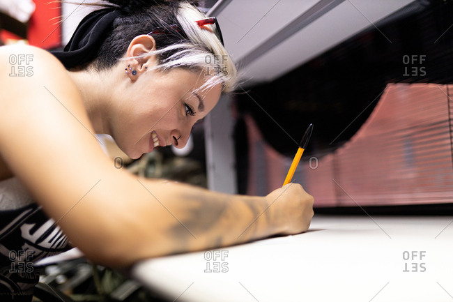 young woman tattoo artist prepares the sketch on the table to start tattooing on the skin