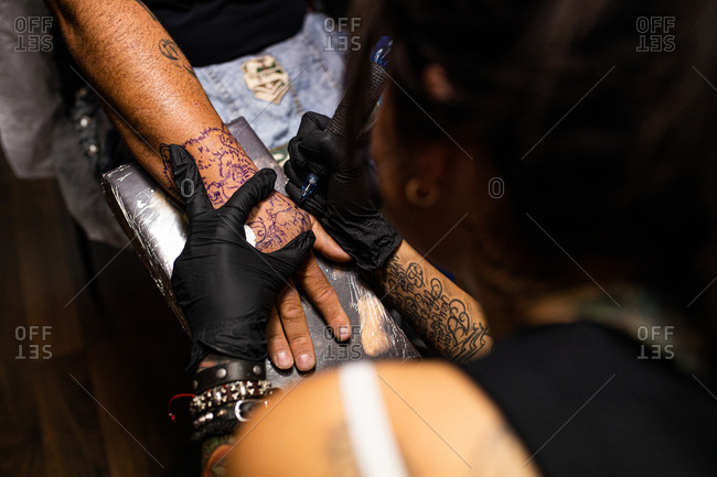 unrecognizable woman tattoo artist tattooing on the skin of one hand
