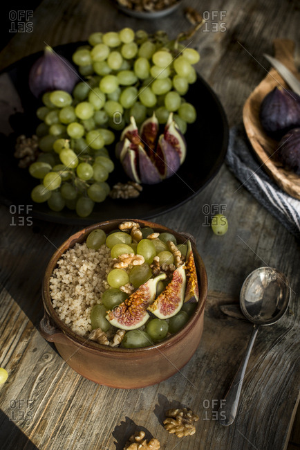 Tunisian couscous called masfouf with fresh fig, raisins, and walnuts in a pottery bowl