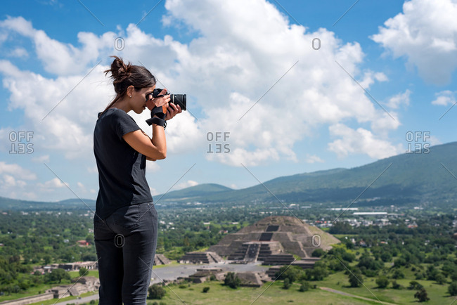 Woman taking photos of the Avenue of the Dead and Pyramid of the Moon at Teotihuacan ruins, Mexico
