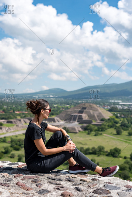 Woman looking at the Avenue of the Dead and Pyramid of the Moon at Teotihuacan ruins, Mexico