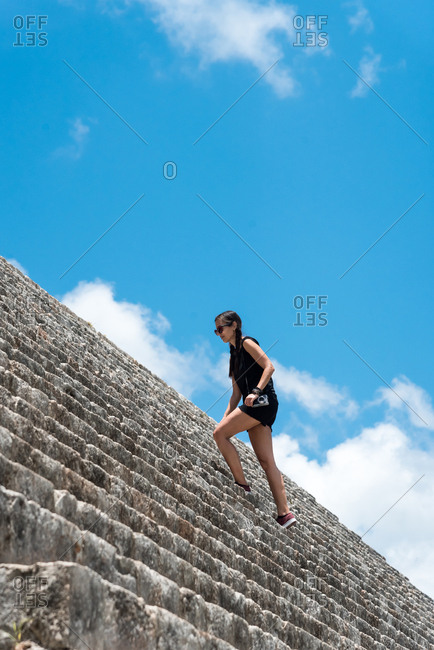 Alone woman climbing stone stairs in the ruins of Uxmal. Yucatan , Mexico
