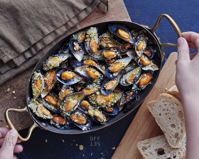 Person placing a pan full of cooked mussels onto wooden board