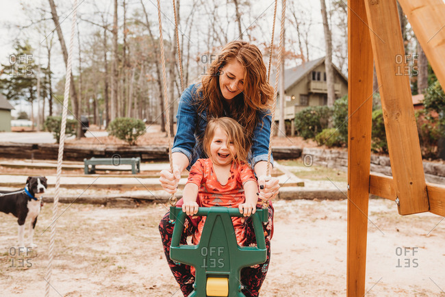 Mother swinging with toddler girl on swing set