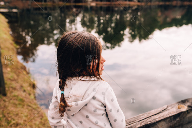 Little girl looking out at lake