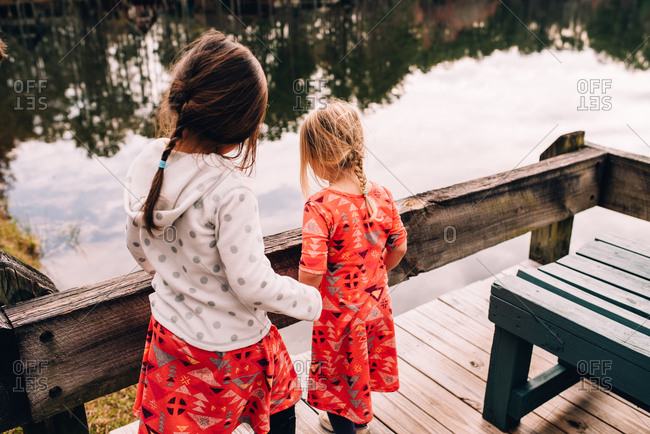 Two little girls standing on dock looking at lake