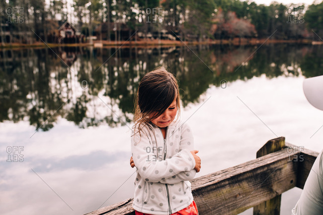Little girl by lake crying and crossing her arms