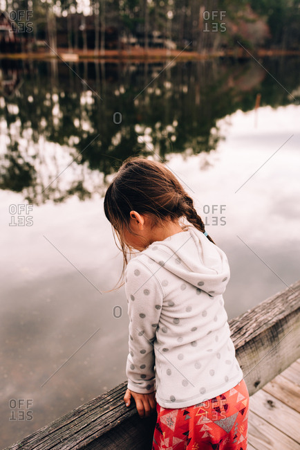 Rear view of a little girl looking out at lake
