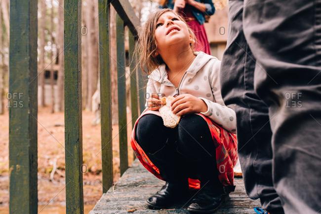 Girl holding bread for feeding ducks on dock