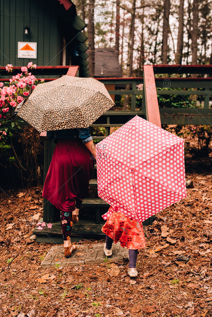 Rear view of little girl walking up steps with mother carrying umbrellas