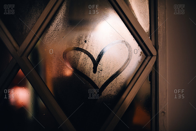 Heart drawn on foggy glass of a door