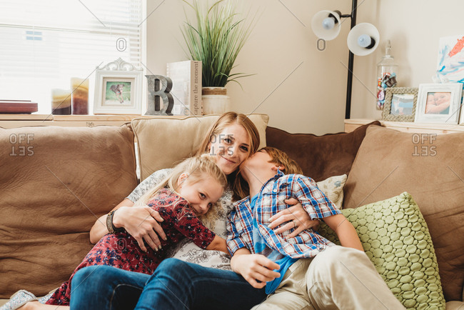 Mother cuddled on sofa with her two children