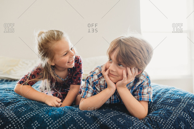 Brother and sister playing on bed