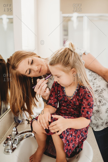 Little girl sitting on bathroom sink while mom does her makeup