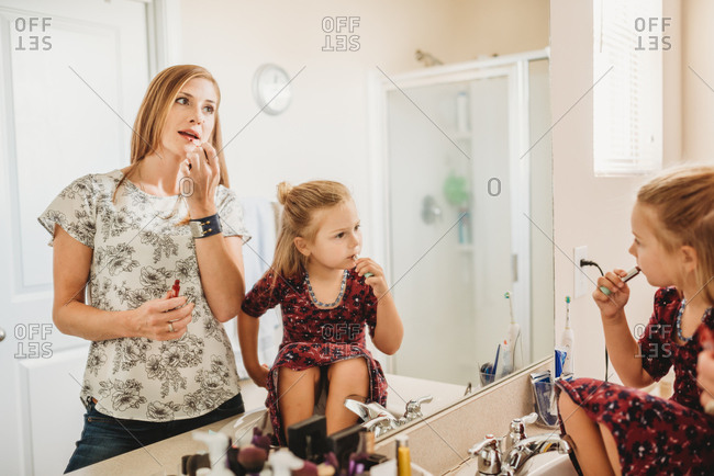Mother and daughter looking in mirror putting on lipstick at the same time