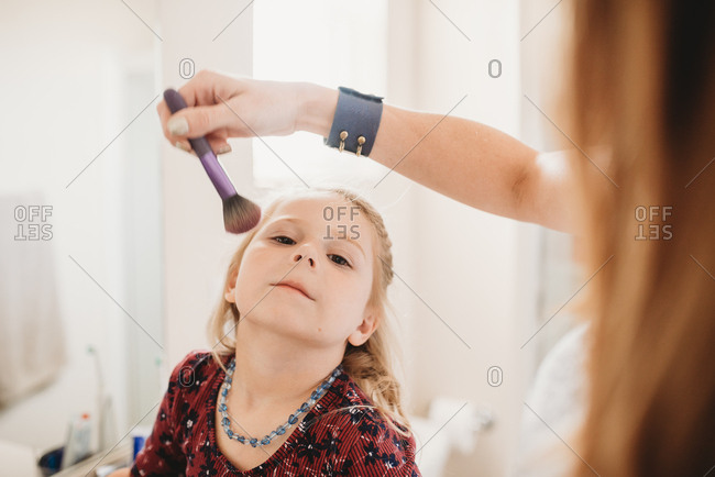 Mother putting blush on little girl's cheeks