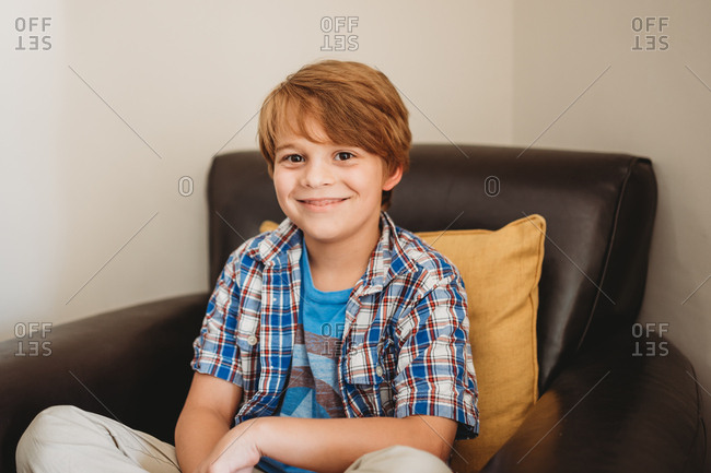Portrait of a little boy with red hair and brown eyes sitting on brown leather chair