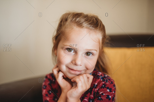Portrait of a little girl with blonde hair and brown eyes sitting on brown leather chair