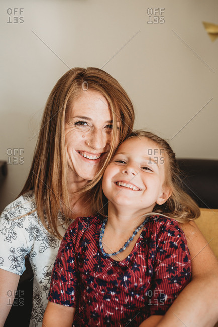 Portrait of a sweet little girl sitting with her mother smiling