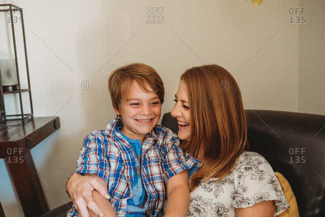Boy with red hair and brown eyes sitting and laughing with mom on leather chair