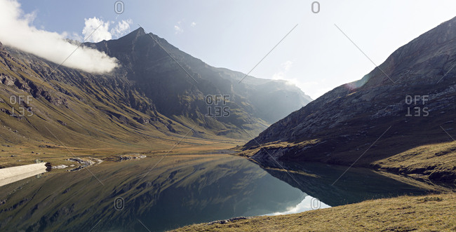 Panorama of calm lake by mountains in the French Alps during summer