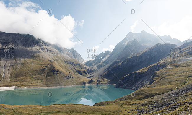 Mountains by turquoise lake in the French Alps during summer
