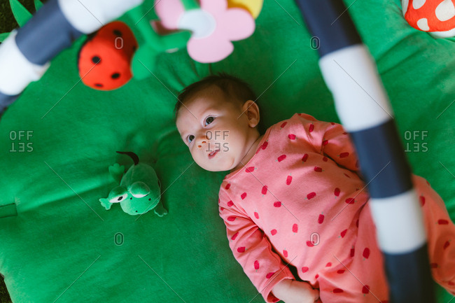 Overhead view of a two month old happy baby girl playing on a child play mat