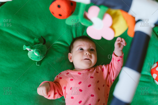 High angle view of a two month old happy baby girl playing on a child play mat