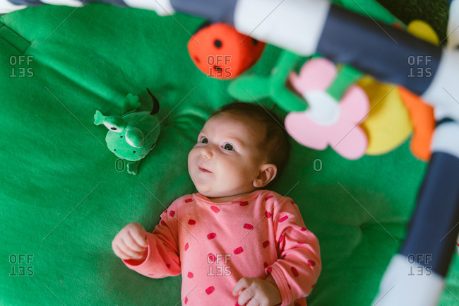 Two month old happy baby girl playing on a child play mat