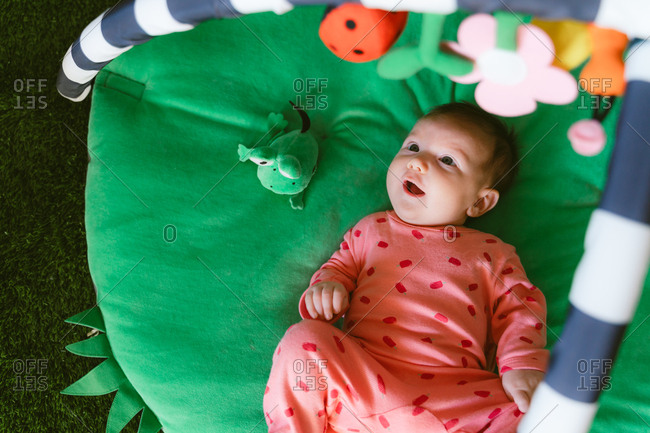 Happy baby girl playing on a child play mat