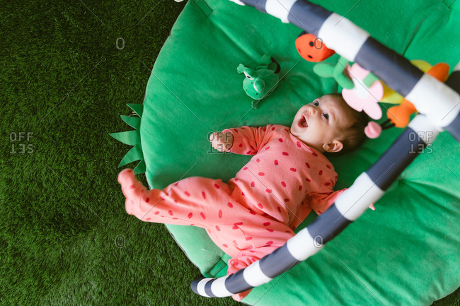 Cute little baby girl playing on a child play mat
