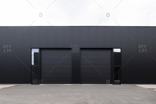 Modern black industrial building with large rolling doors