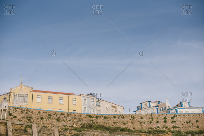 Low angle view of buildings on top of rocky cliff, Ericeira, Portugal