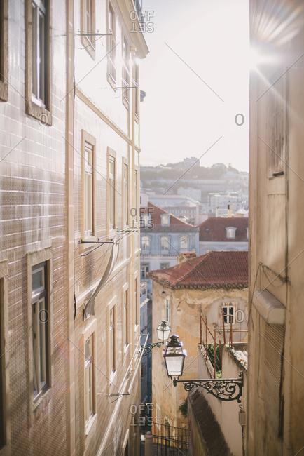 Sun shining between tiled buildings in Lisbon, Portugal