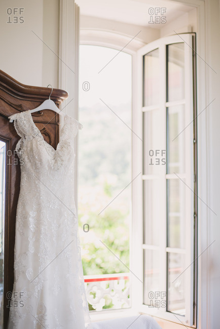 Beautiful wedding gown hanging from armoire by open window