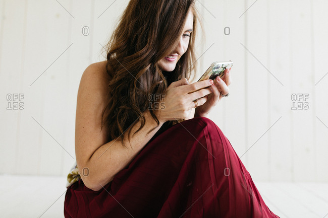 Brunette woman wearing red skirt smiling as she looks at her phone