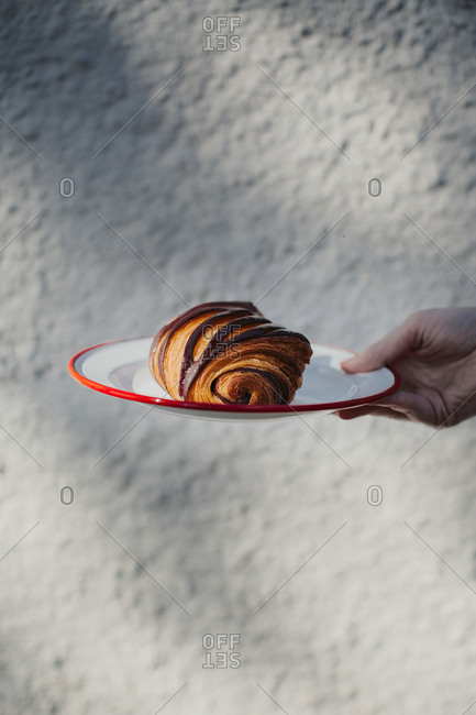 Hand holding a plate with a flaky pain au chocolat against a white textured background