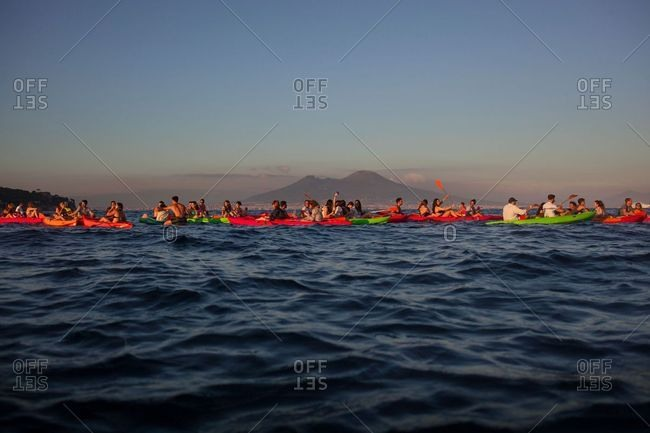 Naples, Italy - June 1, 2018: Group of young adults in kayaking at sunset with the volcano Vesuvius in the background