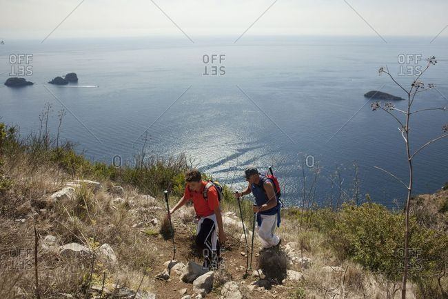 Sorrento, Italy - September 24, 2017: Two mean hiking on a path during a trekking experience on the coast