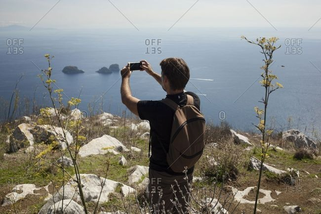Man taking a picture on the top of a hill after a trekking path, Sorrento, Italy