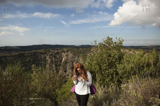 Naples, Italy - November 12, 2017: A ginger woman with her cell phone during a trekking experience on the top of a volcano in Phlegraean Fields