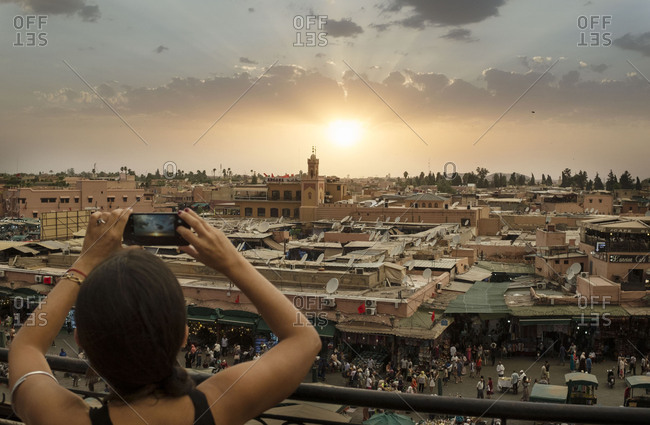 Marrakech, Morocco, Africa - August 6, 2019: Woman taking picture of the beautiful sunset in the square of Jmaa El Fna