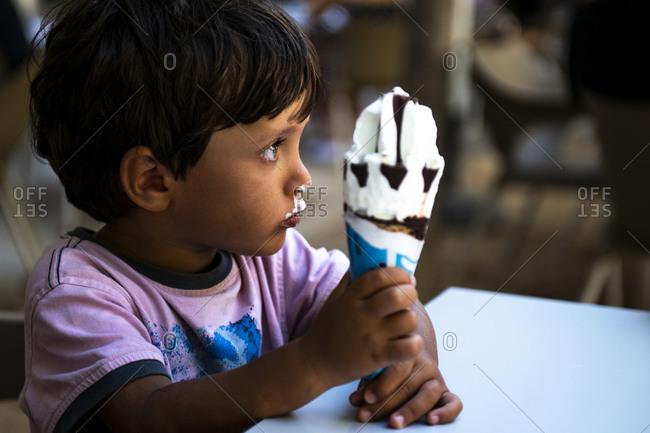Boy eating a vanilla ice cream cone