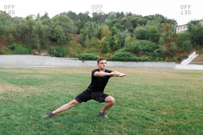 The active boy is doing sport in stadium and leading healthy lifestyle